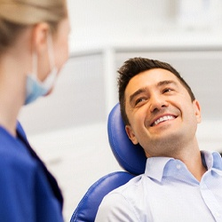 A middle-aged man lying back in a dentist's chair and smiling at his dentist as she explains the process for receiving a dental crown
