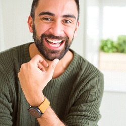 A gentleman wearing a watch and green sweater smiling after receiving his dental bridge