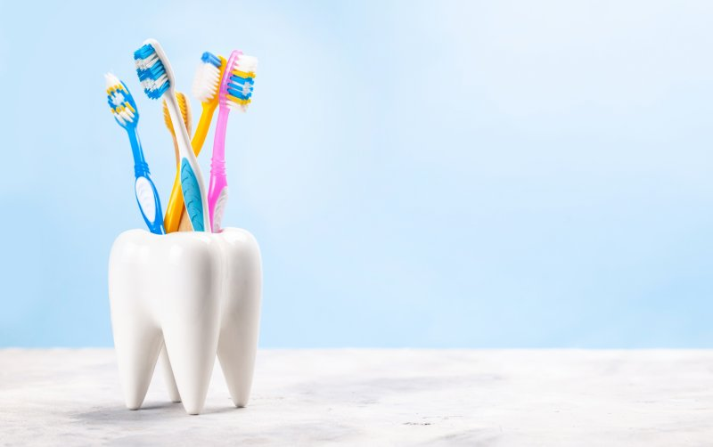 five toothbrushes sitting in a holder that looks like a tooth