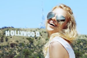 girl smiling with Hollywood sign behind her